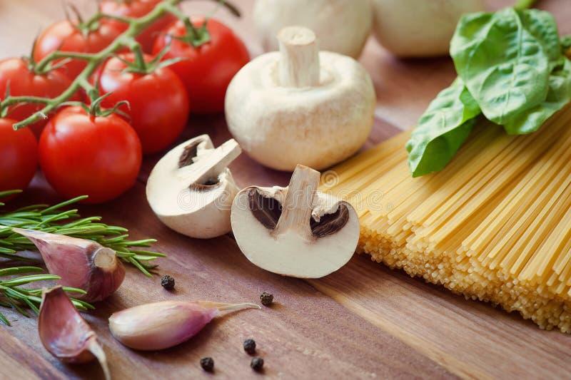Pâtes Spaghetti italiens avec le champignon, la tomate-cerise, le parmesan, le basilic et l'ail Cuisson des pâtes dîner photo libre de droits