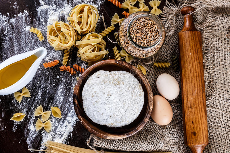 Pâtes sur le fond en bois foncé avec le macro de plan rapproché de la pâte, d'oeufs, de pétrole et de farine image stock