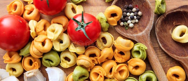 Pâtes, tomates et ail colorés de tortellini sur la table en bois, bannière photographie stock