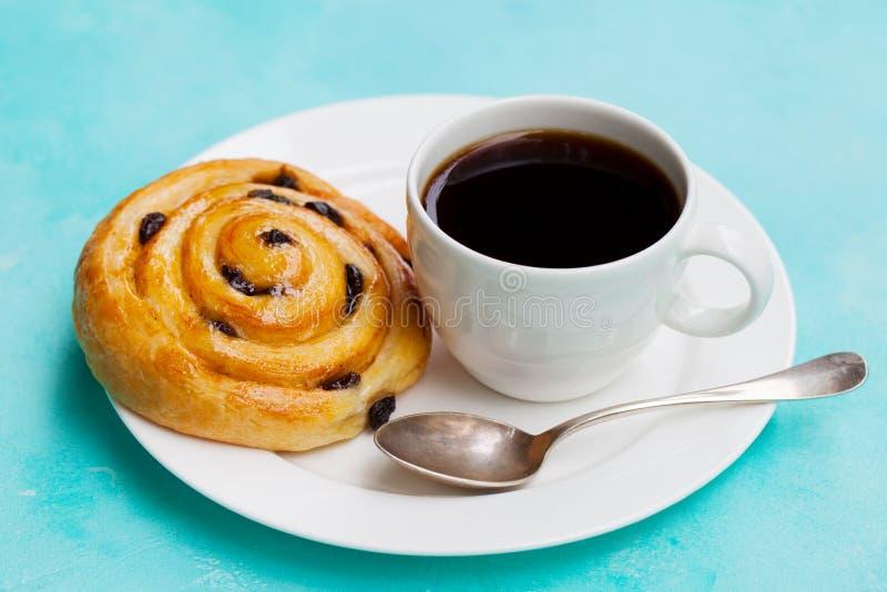 Pâtisserie danoise fraîche avec les raisins secs et la tasse de café noir sur le fond bleu Fin vers le haut photos stock
