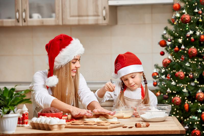 Pâtisserie de Noël de cuisson de mère et de petite fille Les enfants font le pain d'épice cuire au four photographie stock libre de droits