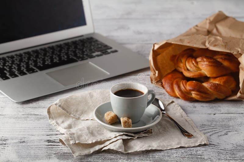 Pâtisserie et tasse fraîches de café de brew sur la table dans le bureau avec le lapt images libres de droits