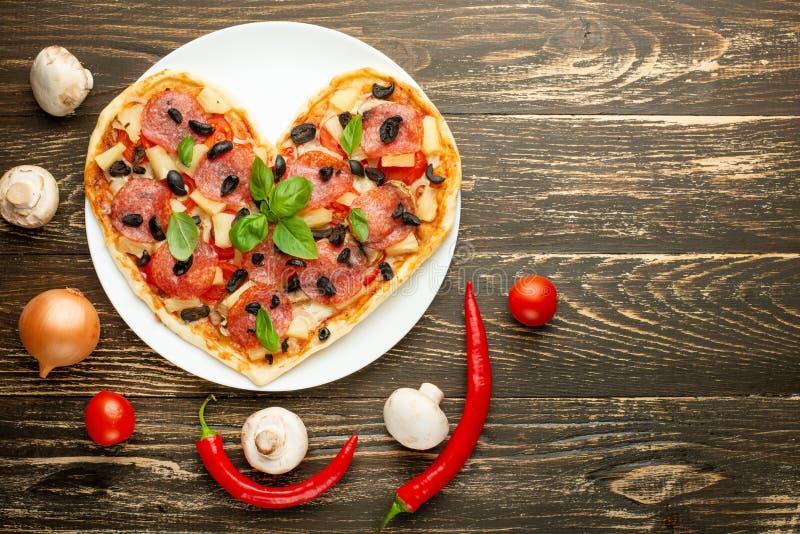 Pâtisseries italiennes de dîner romantique de jour de valentines de concept d'amour de pizza de coeur Sur une table en bois Plat- photos stock