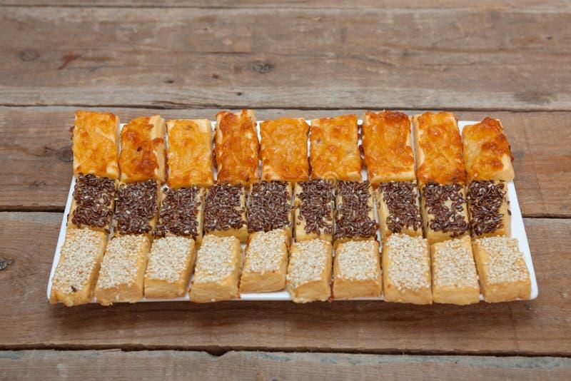 Pâtisseries salées avec du fromage, les graines de sésame et le lin oléagineux photos stock