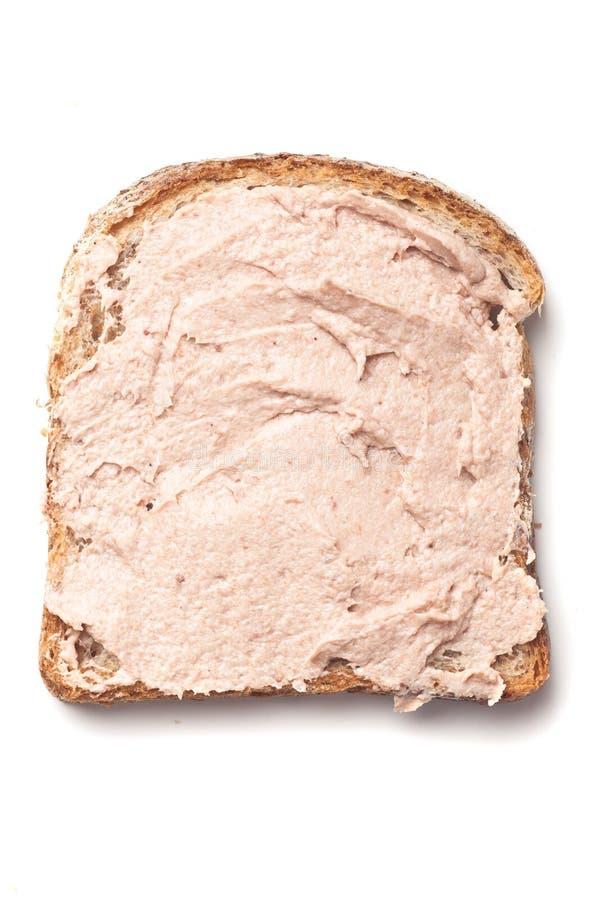 Pâté που διαδίδεται στη φέτα του ψωμιού στοκ φωτογραφία