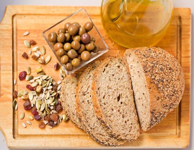 Pão, azeitonas, semente e petróleo verde-oliva. imagem de stock