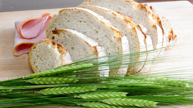 Pão branco com cevada da colheita no fundo de madeira fotografia de stock royalty free