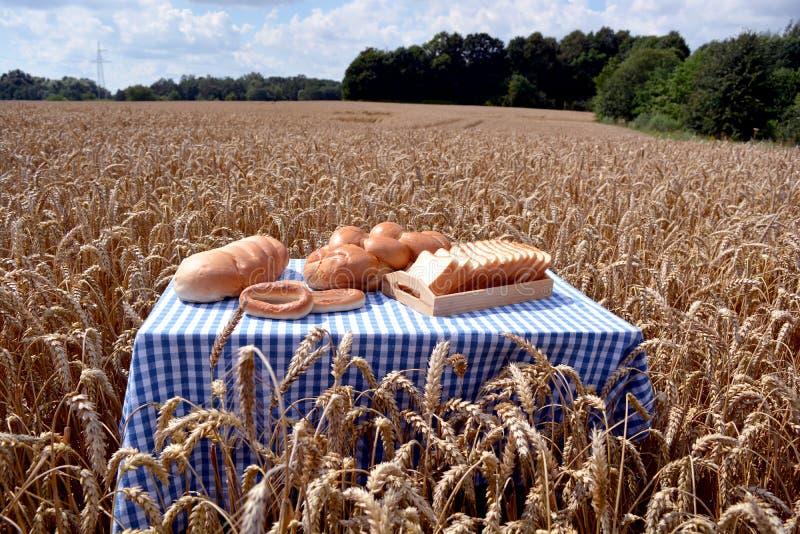 Pão branco na tabela no campo de trigo maduro fotos de stock
