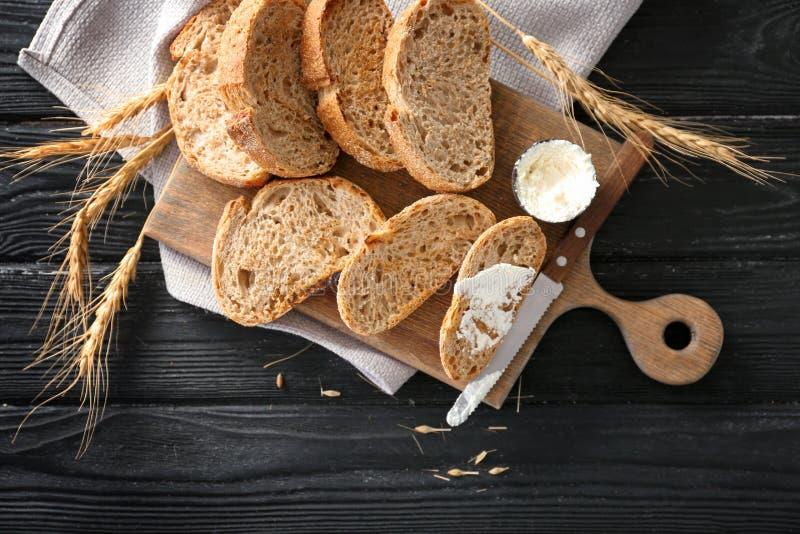 Pão brindado com queijo creme na placa de madeira, vista superior fotografia de stock royalty free