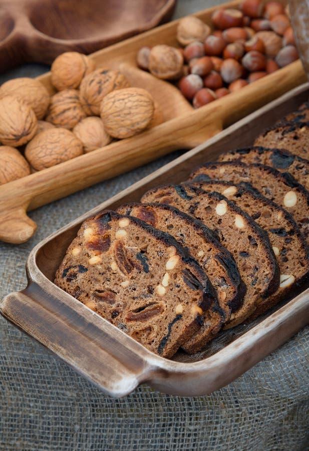 Pão caseiro com frutos e as porcas secados em uma bandeja de madeira, em nozes e em avelã no backgroun, fundo rústico do alimento foto de stock