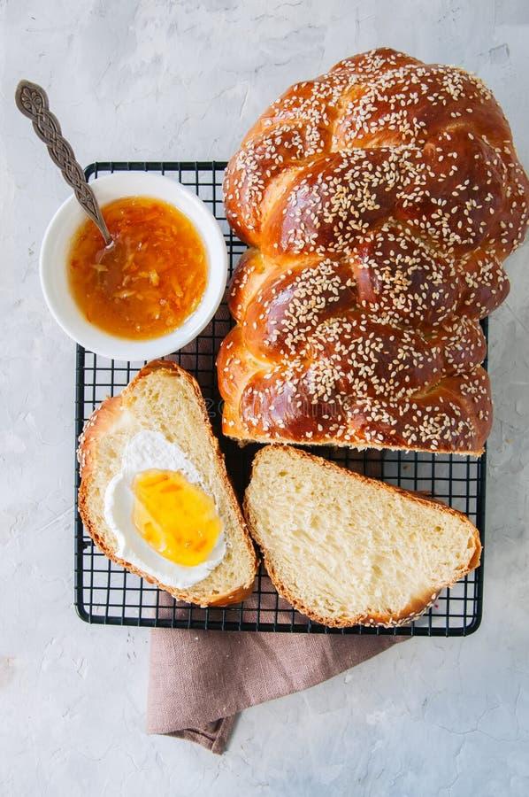 Pão caseiro do Chalá das sementes de sésamo e doce alaranjado em um rac do fio imagem de stock