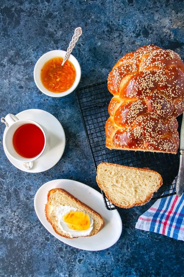 Pão caseiro e chá do Chalá da semente de sésamo em um fundo da pedra azul imagens de stock