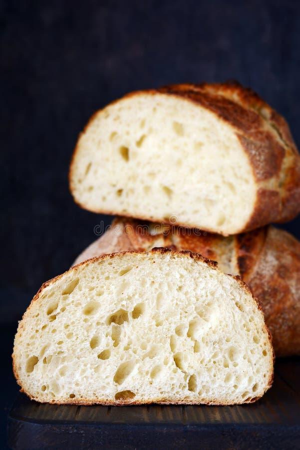 Pão caseiro fresco em um fundo escuro, na farinha de trigo inteiro Forma redonda de pão francês Cozimento do pão unleavened foto de stock