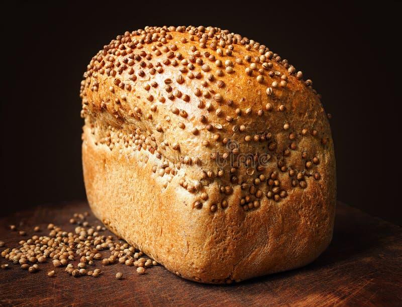 Pão com as sementes de coentro na madeira escura Empilhamento do foco fotografia de stock royalty free