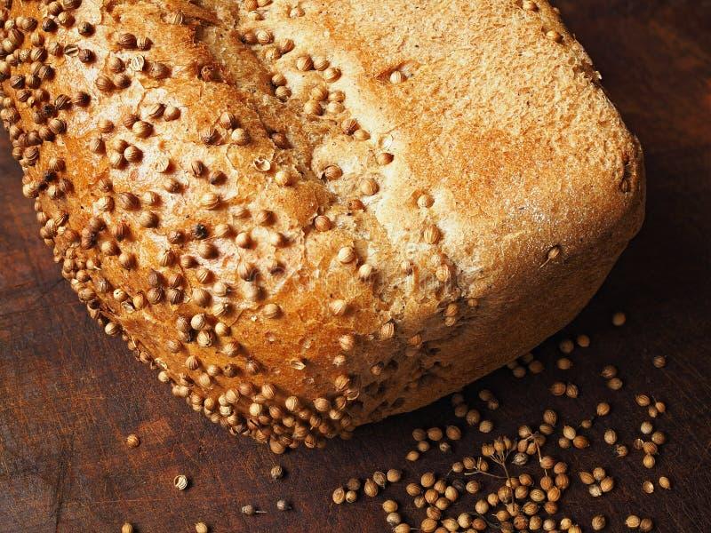 Pão com as sementes de coentro na madeira escura Empilhamento do foco imagens de stock