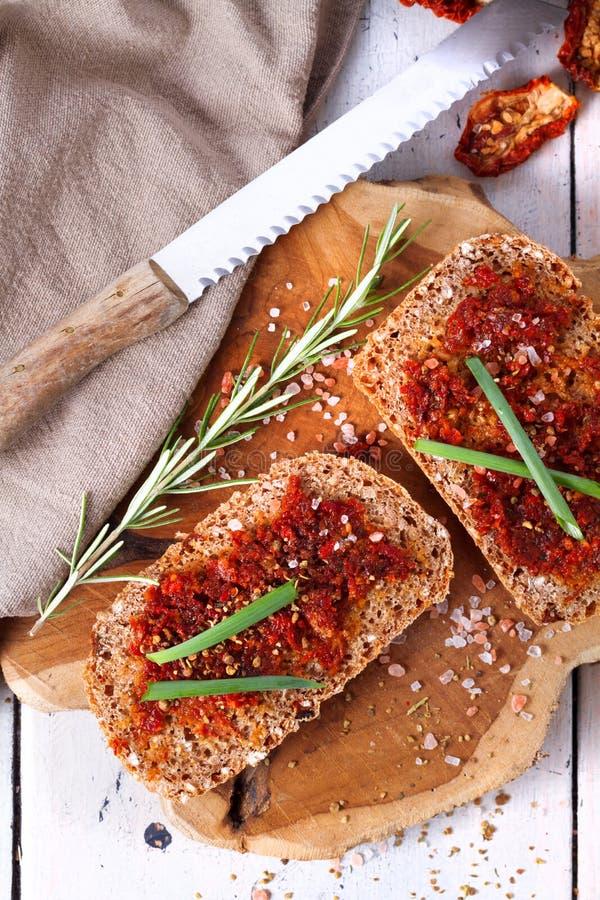 Pão com tomates e as ervas secados imagem de stock