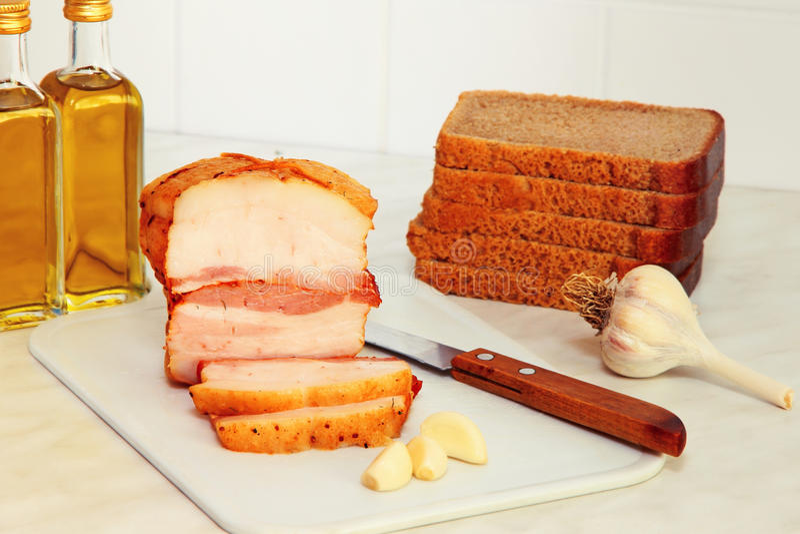 Pão cortado, bacon e óleo vegetal na mesa de cozinha fotos de stock royalty free