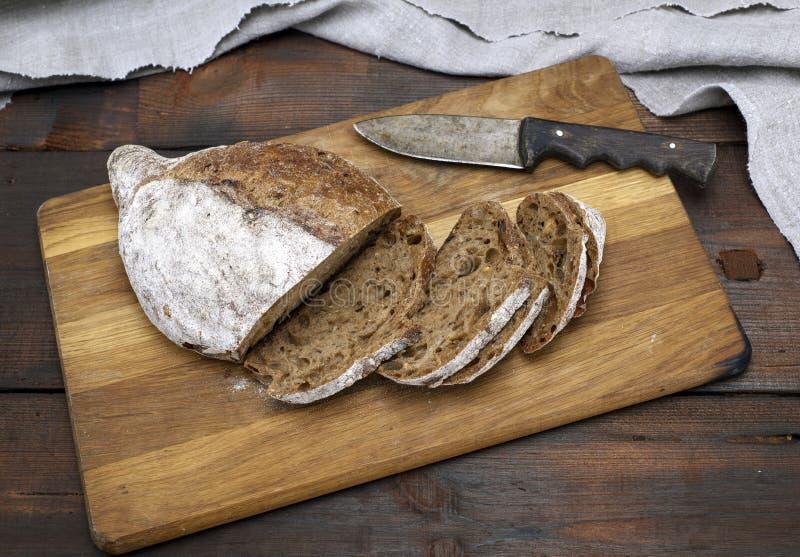 Pão cortado com farinha da farinha de centeio em uma placa de madeira marrom foto de stock royalty free