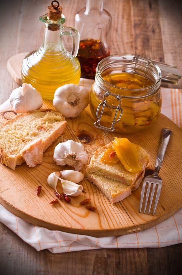 Pão cortado com pimentas sob o petróleo. foto de stock