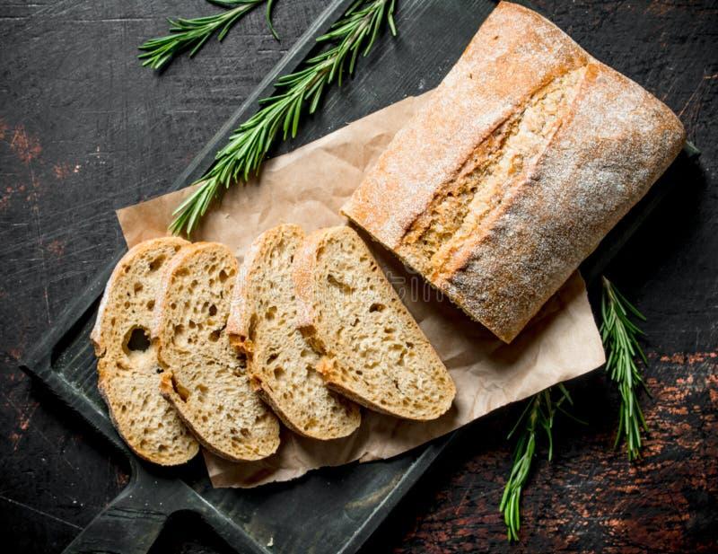 Pão cortado do ciabatta em uma placa de corte com alecrins imagens de stock
