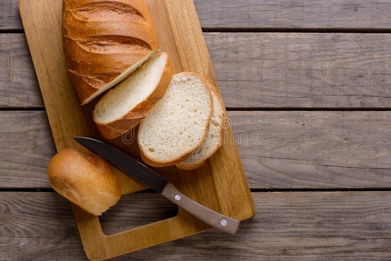 Pão cortado na tabela de madeira imagens de stock royalty free