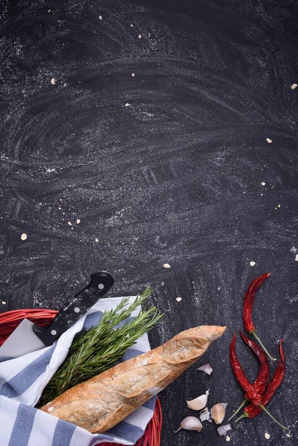Pão cozido fresco na cesta vermelha com pimenta dos alecrins, do alho e de pimentão no fundo escuro Vista superior, espaço do tex fotografia de stock royalty free