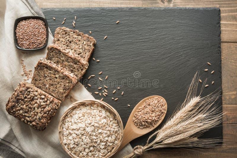 Pão da aptidão Um naco do pão de centeio inteiro rústico fresco com trigo, cortado em um prato e em uma placa pretos da ardósia,  foto de stock royalty free