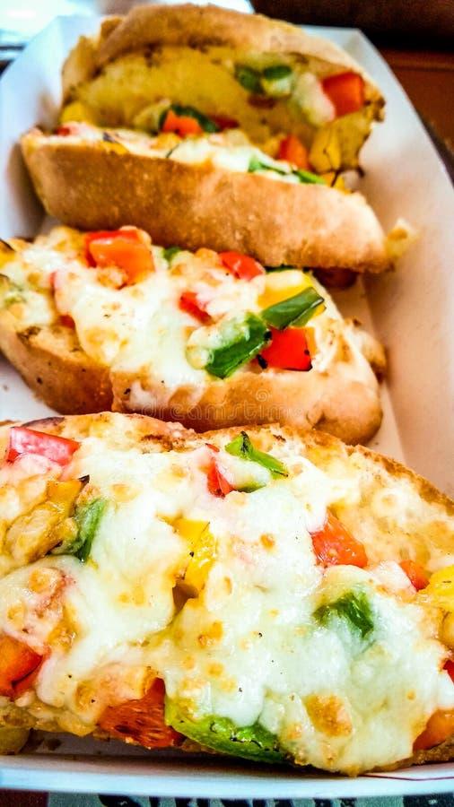 Pão de alho com queijo extra com coberturas fotografia de stock