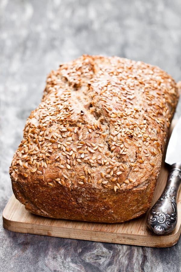 Pão de centeio caseiro do wholemeal com as sementes de linho na tabela de madeira foto de stock