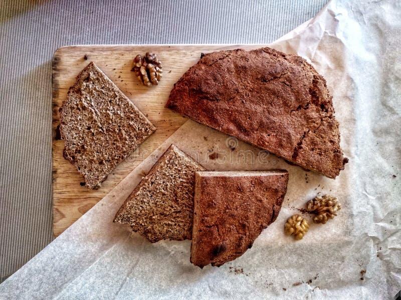 Pão de centeio caseiro recentemente cozido na placa de corte cortado Vista superior foto de stock