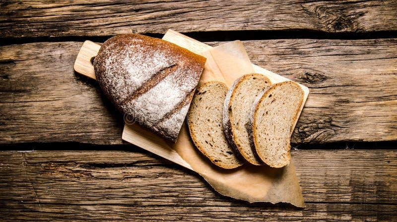 Pão de centeio cortado em uma placa Na tabela de madeira fotos de stock royalty free