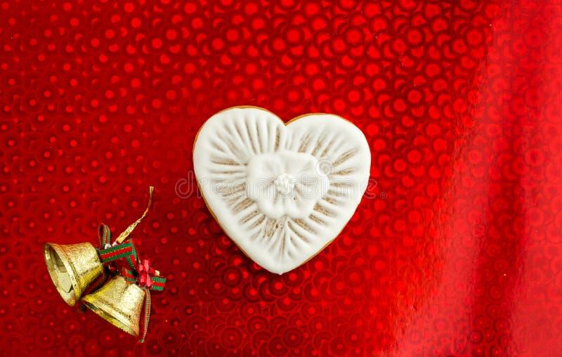 Pão-de-espécie com o esmalte branco na forma do coração em um fundo vermelho Sinos de Natal Configuração lisa imagem de stock