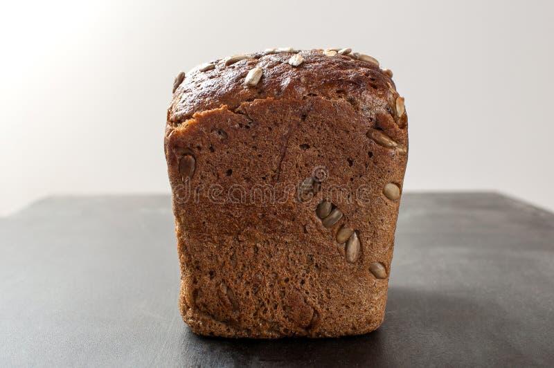 Pão de mistura cozido fresco delicioso com as sementes de girassol do farelo sobre imagem de stock royalty free