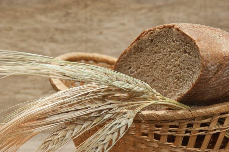 Pão de Rye e orelhas de milho na cesta imagens de stock