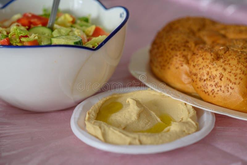 Pão do Chalá em uma tabela para a refeição de Shabbat e hummus caseiro tradicional, salada na tabela cor-de-rosa Culin?ria judaic foto de stock