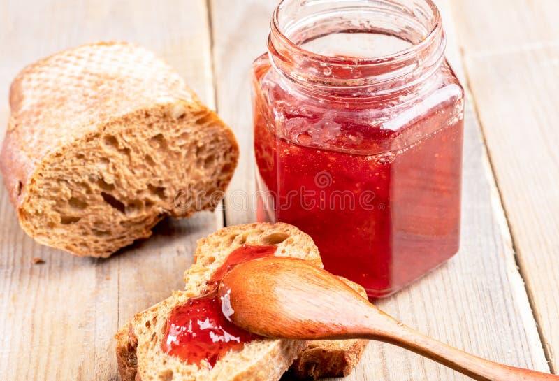 Pão do close-up com doce de morango, colher de madeira, frasco do doce na tabela de madeira imagem de stock royalty free
