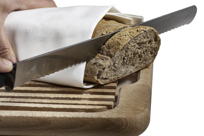 Pão do corte da mão na placa de madeira fotos de stock