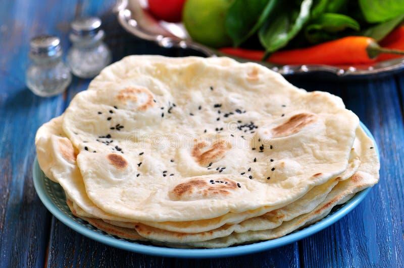 Pão do pão árabe do pão caseiro em um fundo azul imagem de stock