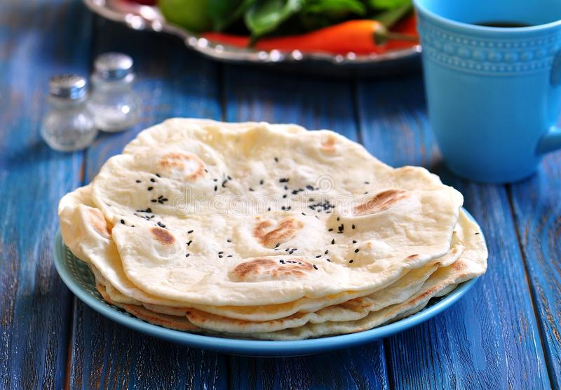 Pão do pão árabe do pão caseiro em um fundo azul fotografia de stock