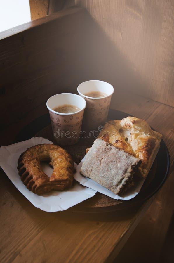 Pão doce fresco da padaria, dois copos de kraft do café preto em uma bandeja de papel, fundo de madeira Conceito da ruptura de ca imagem de stock royalty free