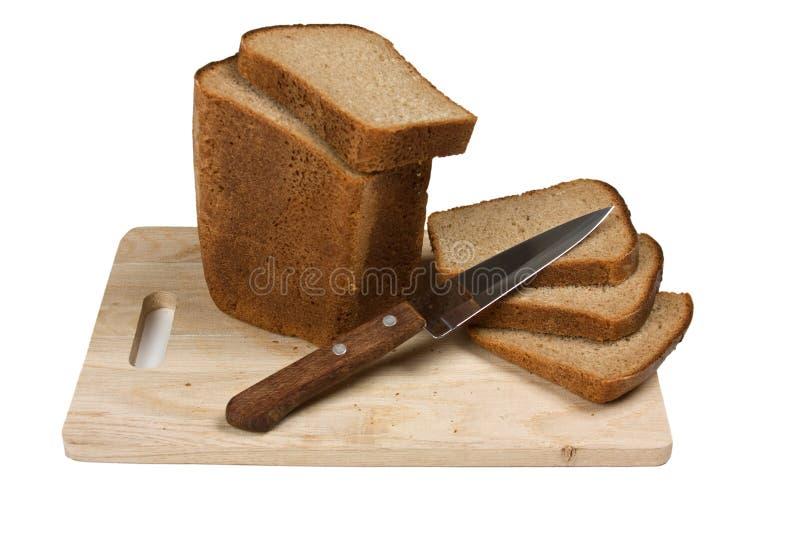 Pão e faca cortados fotografia de stock royalty free