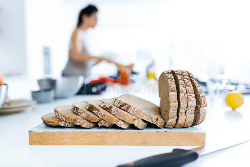 Pão e jovem mulher da aveia que cozinham no fundo fotografia de stock royalty free