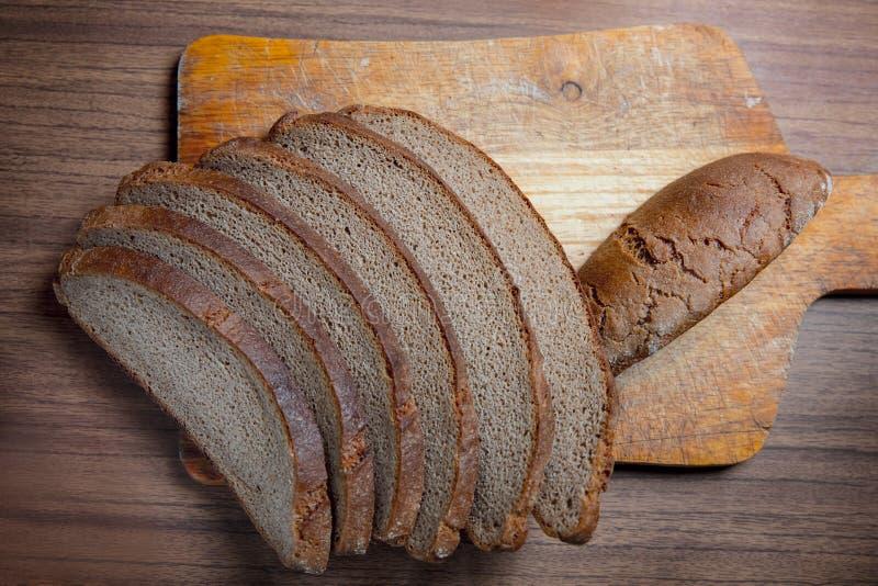 Pão escuro cortado feito da farinha de centeio em uma placa de madeira do corte imagens de stock royalty free