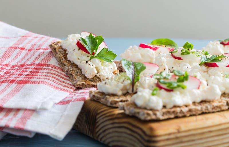 Pão estaladiço com rabanetes e ervas do requeijão foto de stock