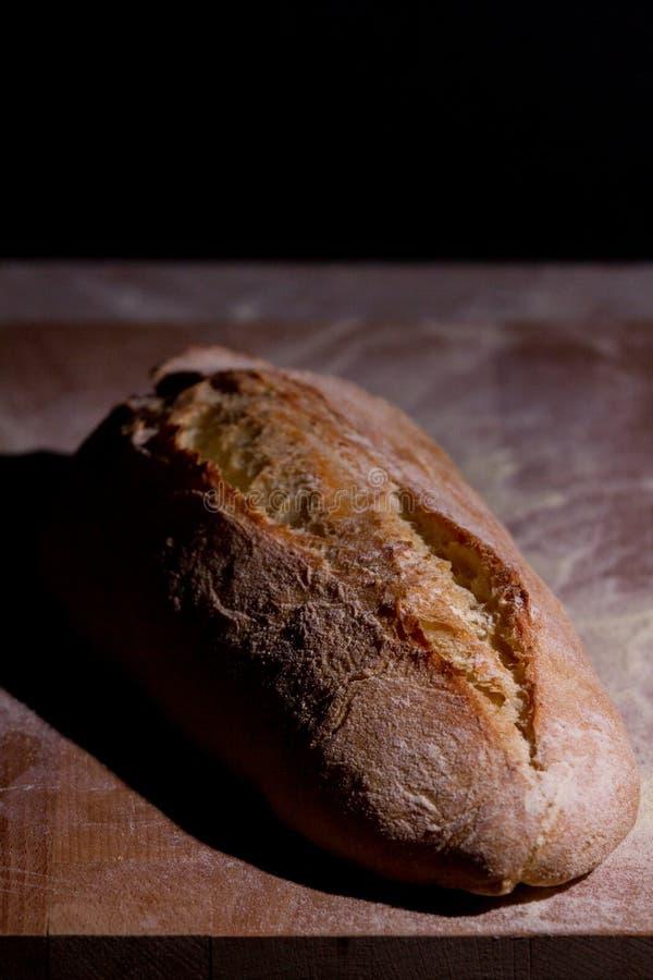 pão Fresco-cozido em uma placa de corte de madeira fotografia de stock royalty free