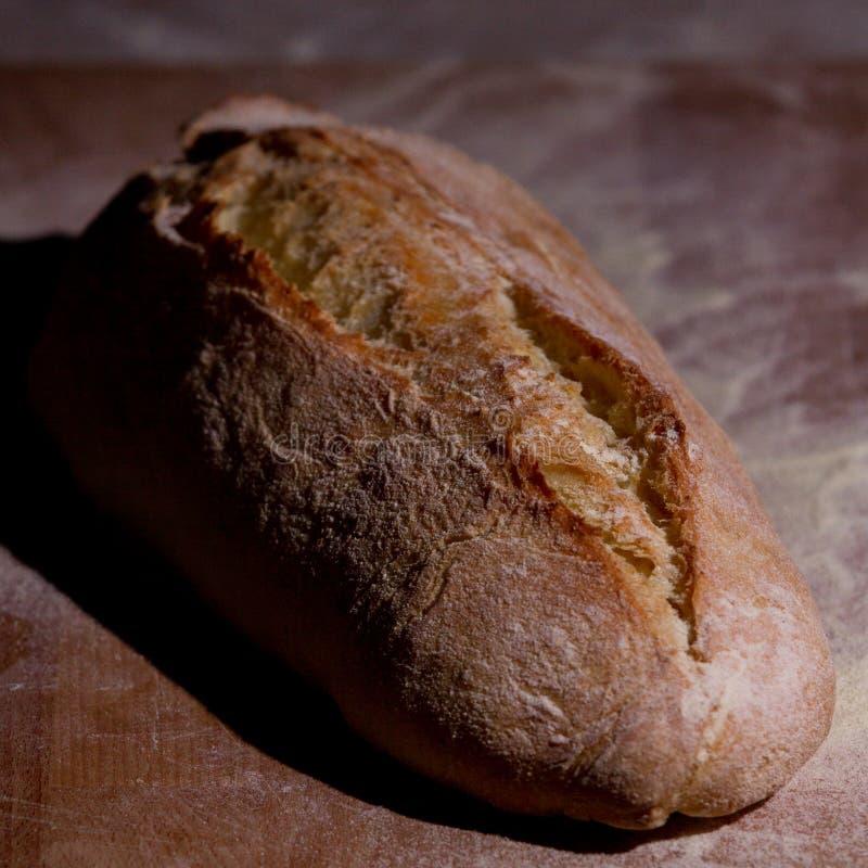 pão Fresco-cozido em uma placa de corte de madeira imagem de stock