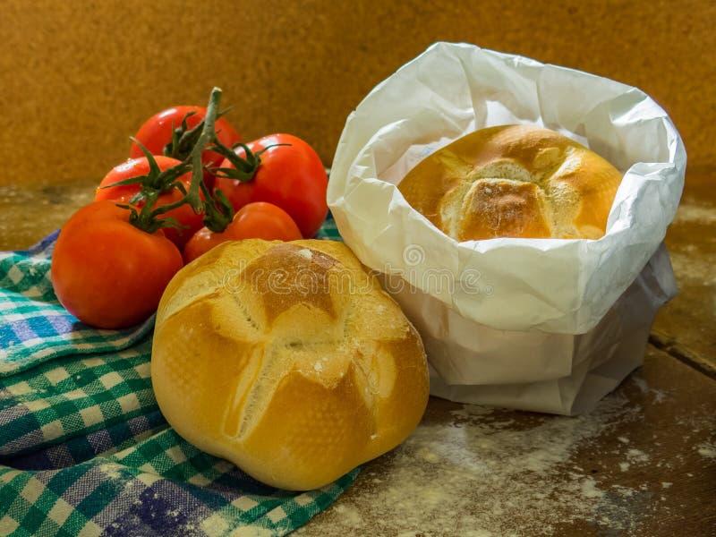 Pão fresco e tomates em uma tabela fotografia de stock royalty free