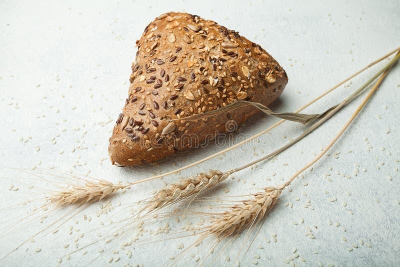 Pão fresco em um fundo branco, orelha da multi-grão do trigo, cevada fotografia de stock