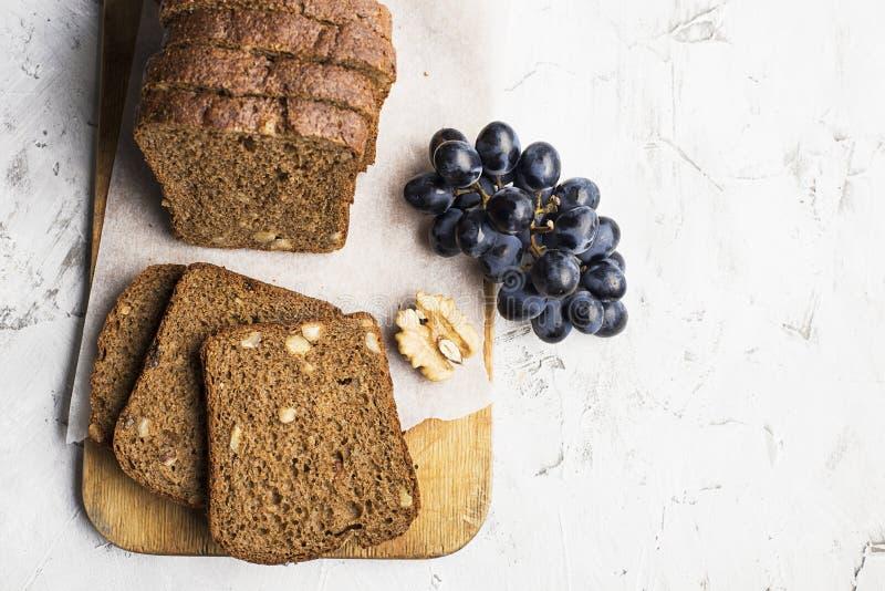 Pão fresco saboroso com noz e passas no fundo claro imagens de stock