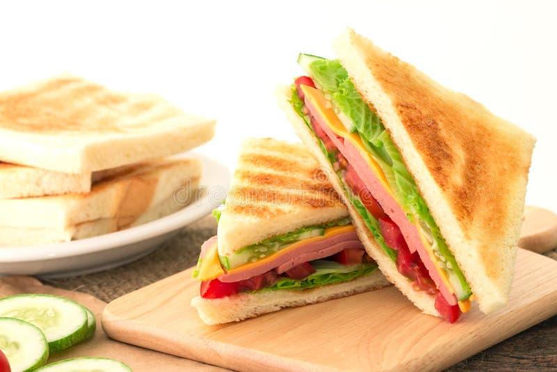 Pão grelhado cortado dos sanduíches com bacon, presunto e queijo com foto de stock